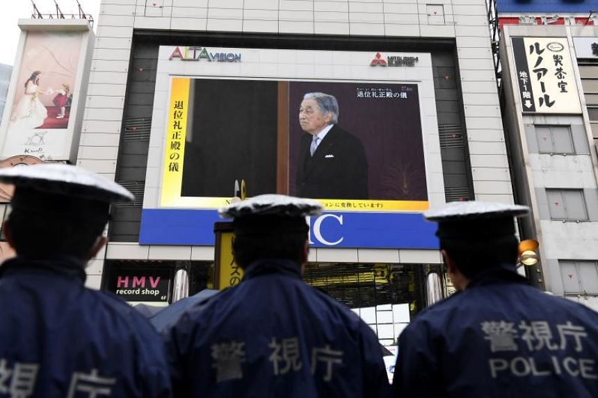 Japanese policemen stand guard as they look at a screen displaying a live coverage of Japanese Emperor Akihito's abdication ceremony in Tokyo, on April 30, 2019.