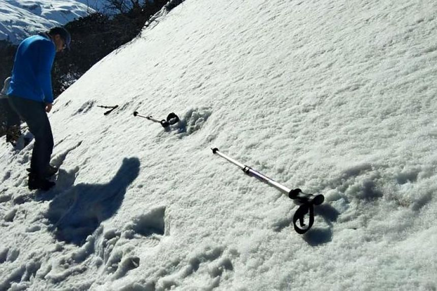 Indian men measure large footprints in the snow, sighted by the Indian Army, near the Makalu Base Camp in the North-Eastern Himalayas, on April 9, 2019.