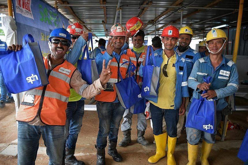 Workers with their Singapore Press Holdings (SPH) goodie bags yesterday. The labourers work on The Woodleigh Residences, an integrated development by Kajima Development and SPH. The gifts were given to mark Labour Day today. ST PHOTO: KUA CHEE SIONG
