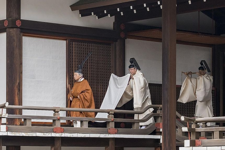 Prime Minister Shinzo Abe (above) and his wife Akie Abe bowing as they arrived for Emperor Akihito's abdication ceremony at the Imperial Palace in Tokyo yesterday. PHOTO: BLOOMBERG Left: Emperor Akihito (far left) attending the Taiirei Tojitsu Kashik