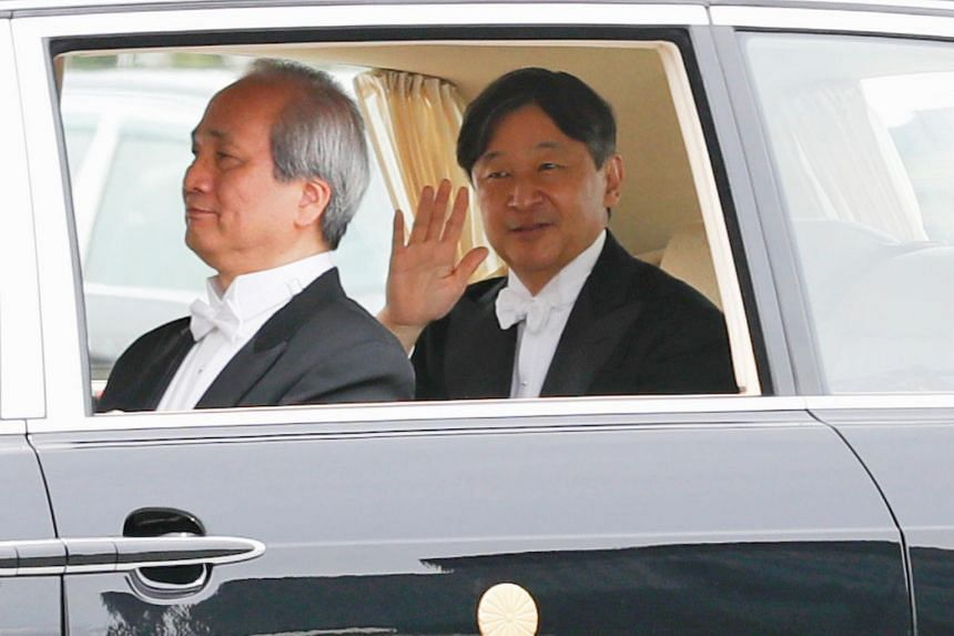 Japan's Emperor Naruhito waves from his vehicle as he leaves the Imperial Palace in Tokyo, Japan on May 1, 2019.