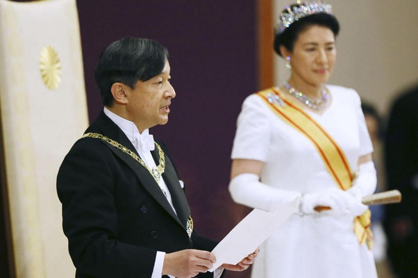 Japan's Emperor Naruhito, flanked by Empress Masako, delivers a speech during a ceremony called Sokui-go-Choken-no-gi, at the Imperial Palace in Tokyo, on May 1, 2019.