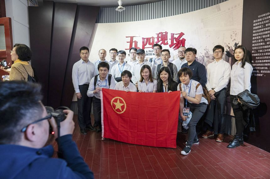 Visitors taking a photo with a Chinese Communist Youth League flag at an exhibition in the New Culture Movement Memorial Museum in Beijing late last month. On May 4, 1919, students led a protest against Western colonialism that inflamed Chinese natio