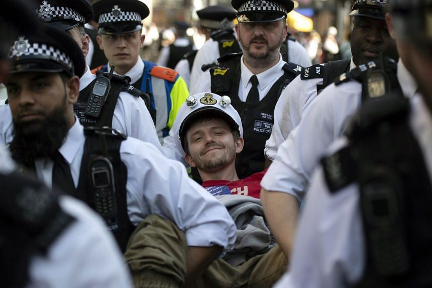 An Extinction Rebellion climate change protester is detained by police at Oxford Circus in London.