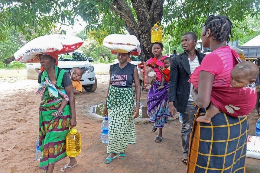 Women carry food and water aid in northern Mozambique, following the passage of Cyclone Kenneth.