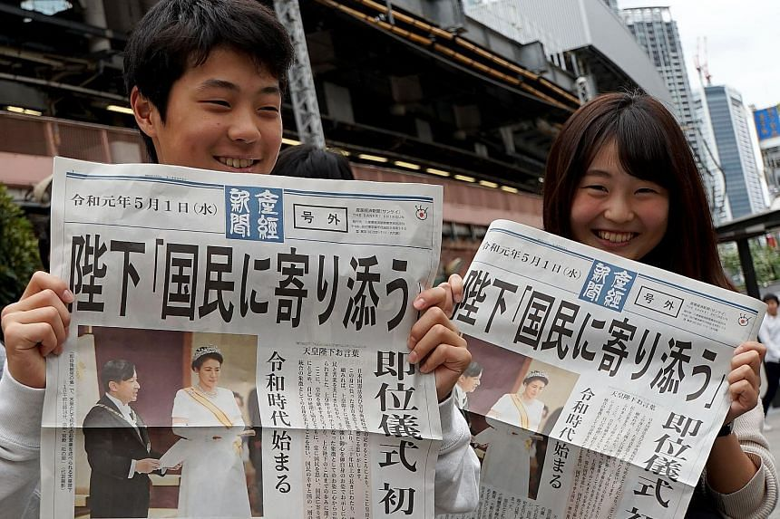 People in Tokyo yesterday showing a newspaper's extra edition reporting Emperor Naruhito's accession to the throne.
