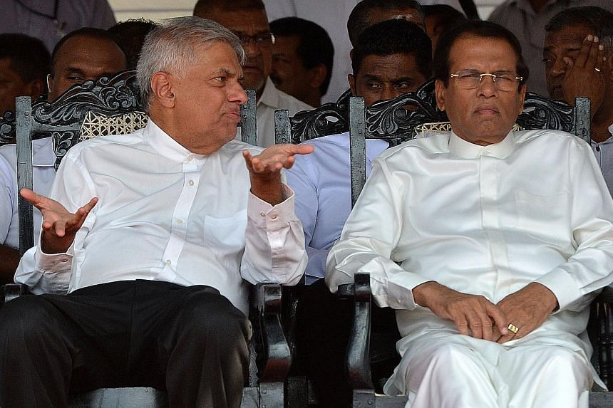 Sri Lanka's Prime Minister Ranil Wickremesinghe (left) and President Maithripala Sirisena at a public event yesterday. Many Sri Lankans believe a rift between both leaders has undermined national security. A Sri Lankan Muslim woman and a man being ch