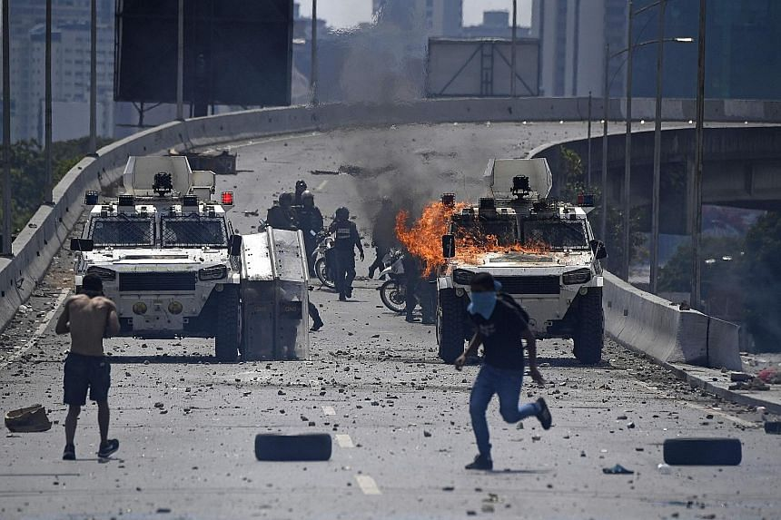 Supporters of Venezuelan opposition leader and self-proclaimed interim president Juan Guaido clashing with forces loyal to President Nicolas Maduro on Tuesday. More than 100 people were injured in the anti-Maduro protests as tens of thousands of peop