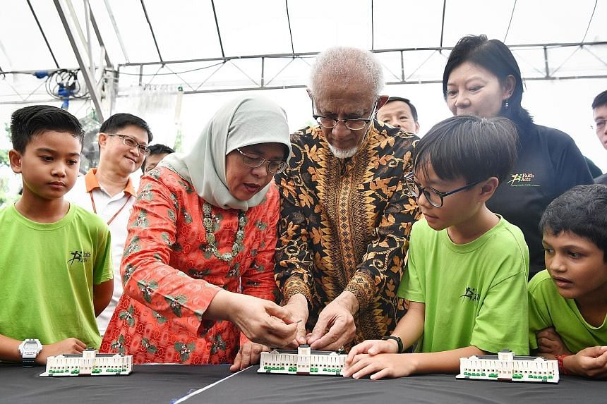 The model, created with 200 Lego bricks, was commissioned by the President's Office and unveiled to commemorate the Istana's 150th anniversary this year. Seven-year-old Ong Ryu Joon (in red shirt), with his father Michael Ong (in green), launching a