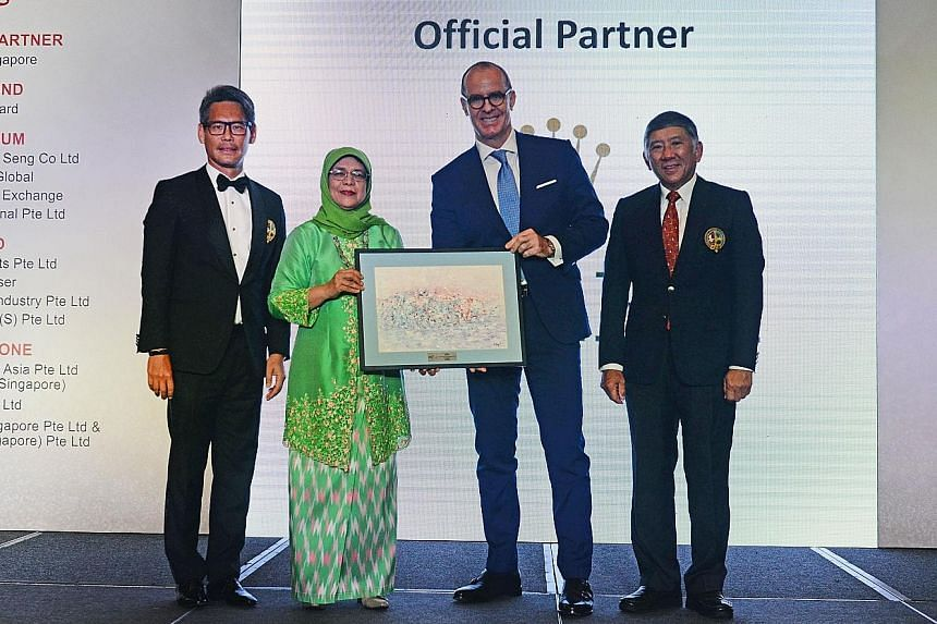 President Halimah Yacob presenting a token of appreciation to Chris Gisi, CEO of Rolex Singapore and official partner of this year's Singapore Island Country Club (SICC) 48th May Day Charity last night. Also present on stage were the organising chair