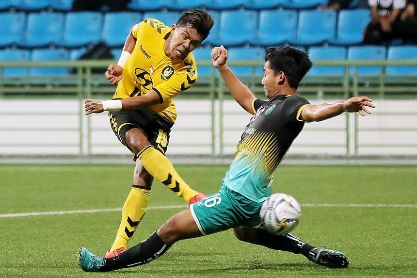 Tampines Rovers' hat-trick hero Khairul Amri taking a shot past lunging Yangon United defender Thu Rein Soe in their AFC Cup Group F match at the Jalan Besar Stadium yesterday. Tampines won 4-3.