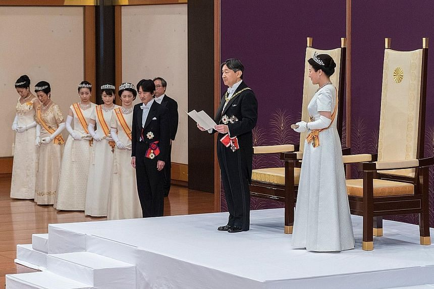 Emperor Naruhito, with Empress Masako beside him, giving a speech during a ceremony inside the Imperial Palace in Tokyo yesterday. Emperor Naruhito is Japan's 126th ruler in the world's oldest hereditary monarchy.