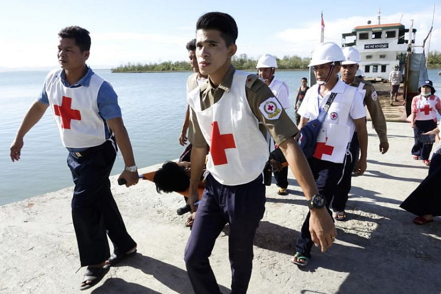 Members of Myanmar Red Cross society carry a wounded Rakhine ethnic man as they move injured people from a boat to Sittwe hospital in Myanmar's Rakhine state on May 2, 2019.