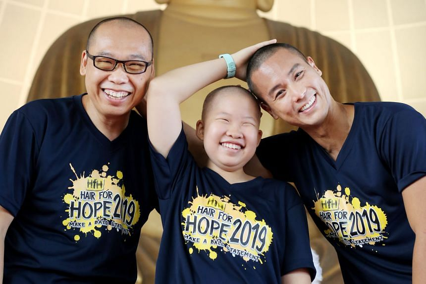 (From left) Mr Chong Hui Kwee, Joanna Chong and actor Andie Chen with freshly shaved heads in support of the Hair for Hope event, organised by the Children's Cancer Foundation (CCF). Through the event, CCF aims to raise awareness of childhood cancer.