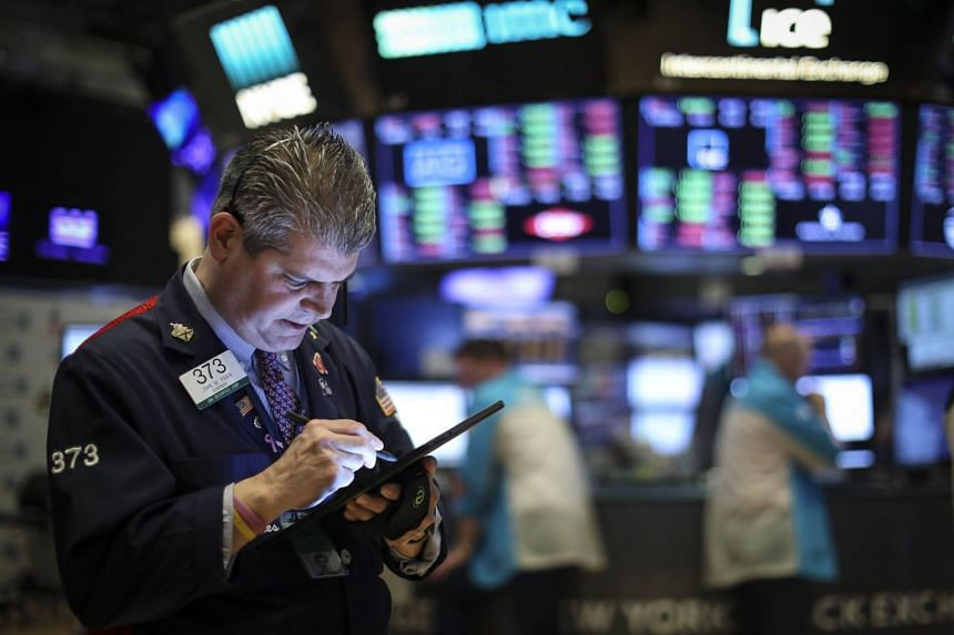 Traders and financial professionals work on the floor of the New York Stock Exchange ahead of the closing bell.