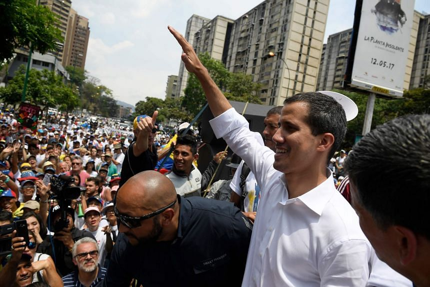 Venezuelan opposition leader Juan Guaido gestures at supporters during a rally to commemorate May Day.