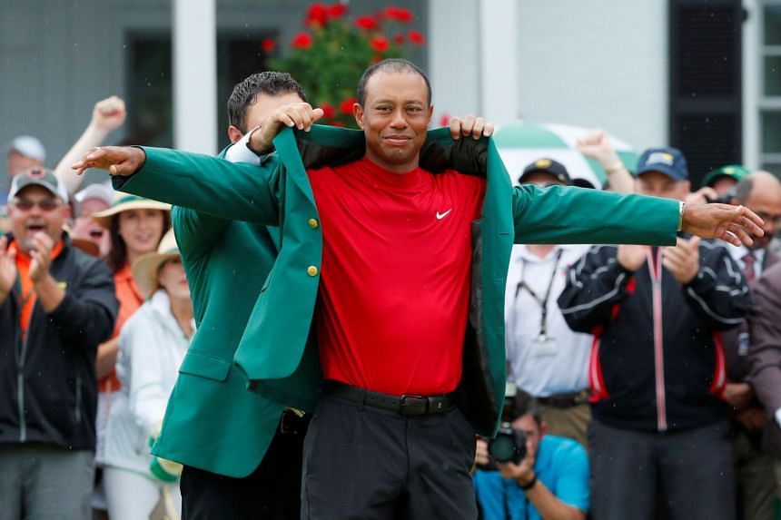 Patrick Reed places the green jacket on Tiger Woods, after Woods won the 2019 Masters in Augusta, Georgia.