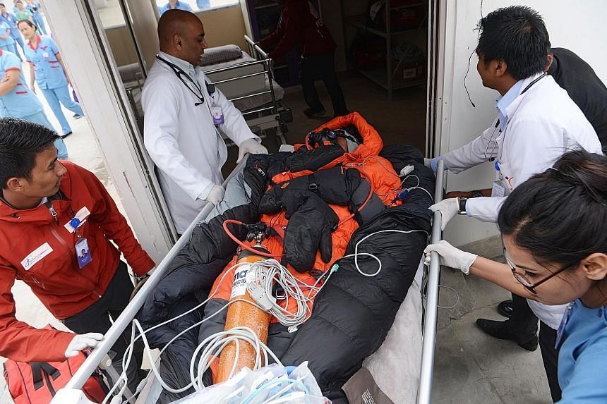 Medical staff and rescue personnel moving Malaysian climber Chin Wui Kin to a hospital bed after airlifting him to Mediciti Hospital in Lalitpur, on the outskirts of Kathmandu, last Friday. Dr Chin, whose condition was described as critical, was tran