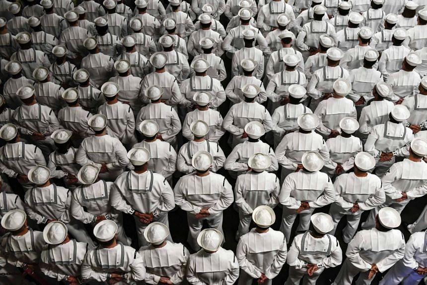 US sailors stand at parade rest during a Change of Command ceremony aboard the amphibious assault ship USS Wasp in Subic Bay, Philippines, on April 13, 2019.