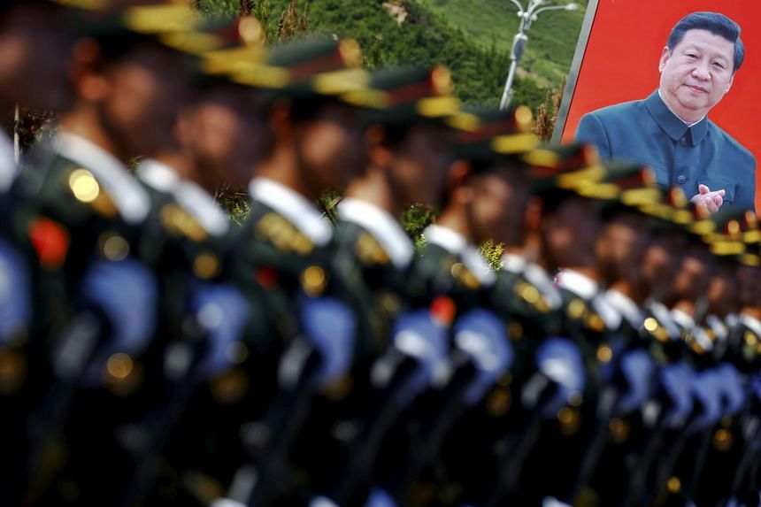 A picture of Chinese President Xi Jinping seen behind soldiers of the People's Liberation Army during a training session for a military parade.