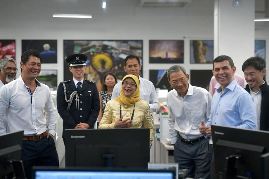 President Halimah Yacob touring The Straits Times' newsroom on May 3, 2019. With her are Singapore Press Holdings chairman Lee Boon Yang (third from right), SPH deputy chief executive Anthony Tan (right), ST editor Warren Fernandez (second from right