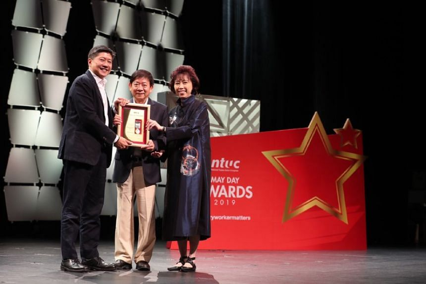 Minister for Transport Khaw Boon Wan receiving the Medal of Honour from National Trades Union Congress secretary-general Ng Chee Meng and NTUC president Mary Liew.
