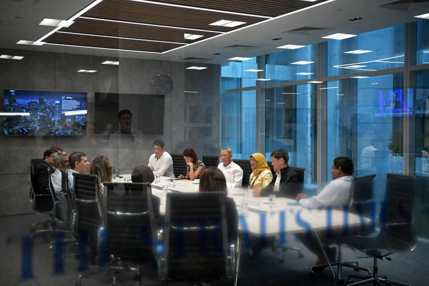 President Halimah Yacob in a meeting room of The Straits Times' newsroom. To her right is Singapore Press Holdings chairman Lee Boon Yang and to her left is SPH deputy chief executive Anthony Tan. Across the table from Madam Halimah is ST editor Warr