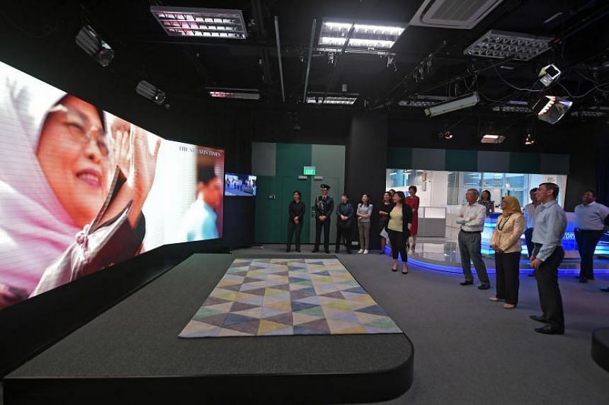President Halimah Yacob touring the new SPH Studios in The Straits Times' newsroom on May 3, 2019. She  watches a video produced as part of a multimedia project by ST, in collaboration with the Istana, to mark the 150th anniversary of the presidentia