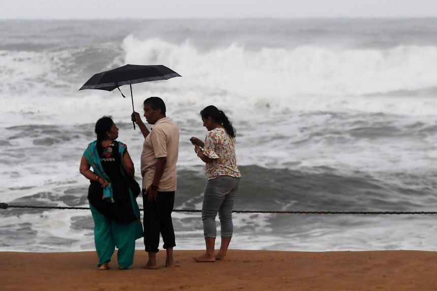 People stand on a closed beach in Puri as cyclone Fani approaches.