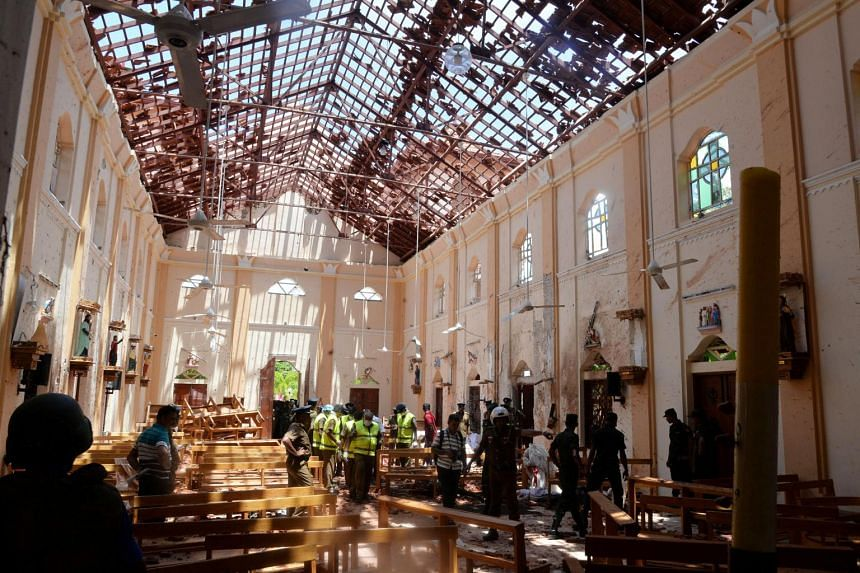 Crime scene officials inspect the site of a bomb blast inside a church in Negombo, Sri Lanka, on April 21, 2019.