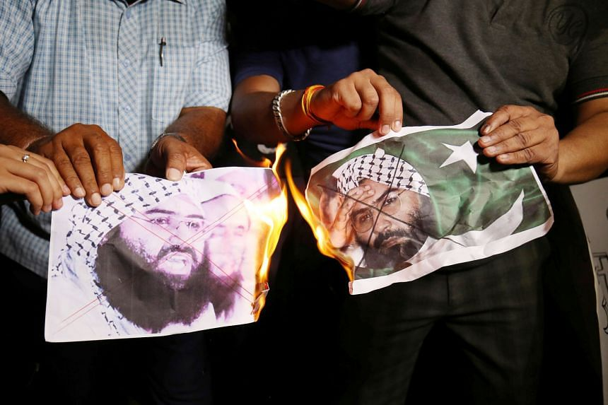 Indians burning pictures of Masood Azhar, head of the Pakistan-based militant group Jaish-e-Mohammed, as they celebrated the UN Security Council committee's decision on Wednesday to blacklist the terrorist.