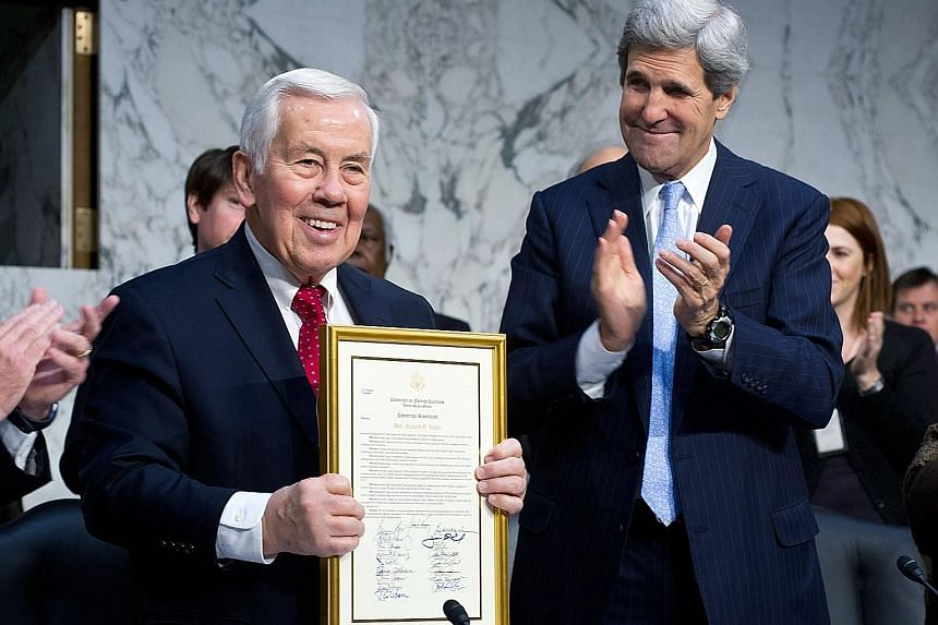 Then Senator Richard Lugar (left) receiving an award from his Senate colleagues, including committee chairman Senator John Kerry during the Senate Foreign Relations Committee hearings on Capitol Hill in 2012.