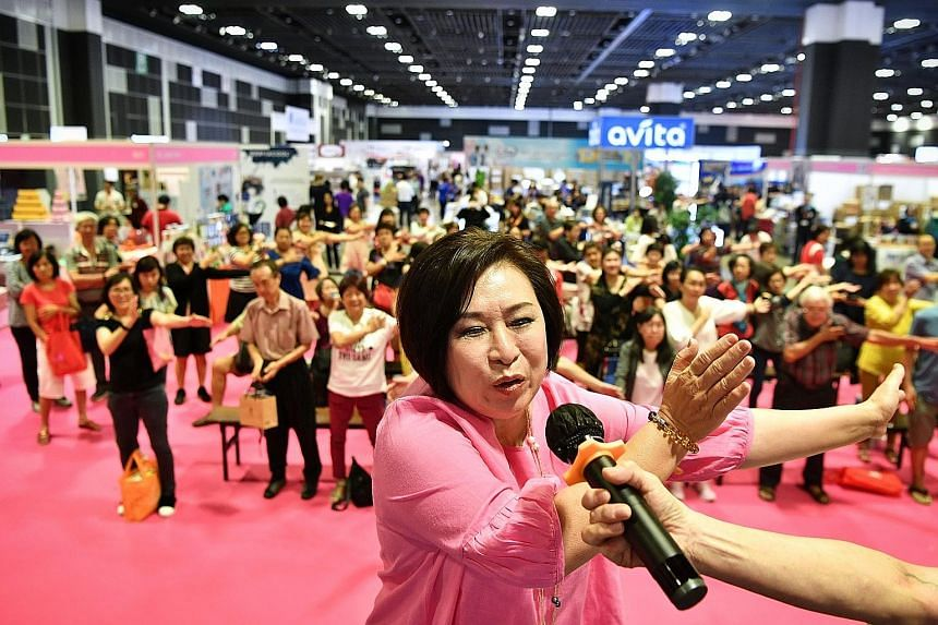 Ms Xiao Caiying leading a mass meridian detox exercise at the Health Fiesta at Suntec Singapore yesterday. ST PHOTO: CHONG JUN LIANG