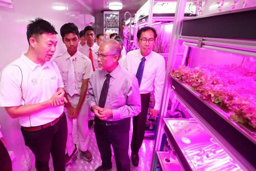 Founder of Life3 Biotech Ricky Lin (left) and National Junior College principal Ang Pow Chew (right) giving Minister for the Environment and Water Resources Masagos Zulkifli a tour of National Junior College's Agriculture-Technology Facility, on Ma