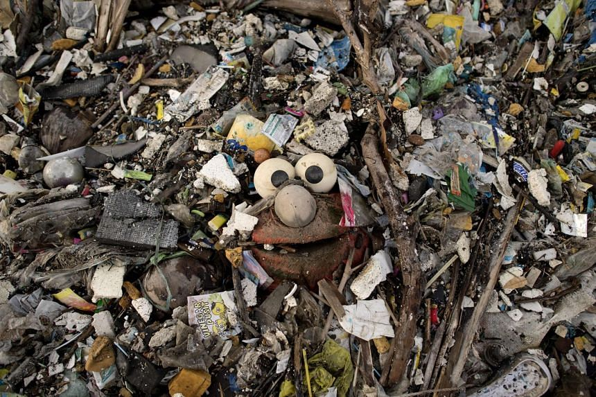 "A stuffed toy of the Sesame Street character ""Elmo"" is seen, surrounded by plastic waste on a beach on the Freedom island critical habitat and ecotourism area near Manila."