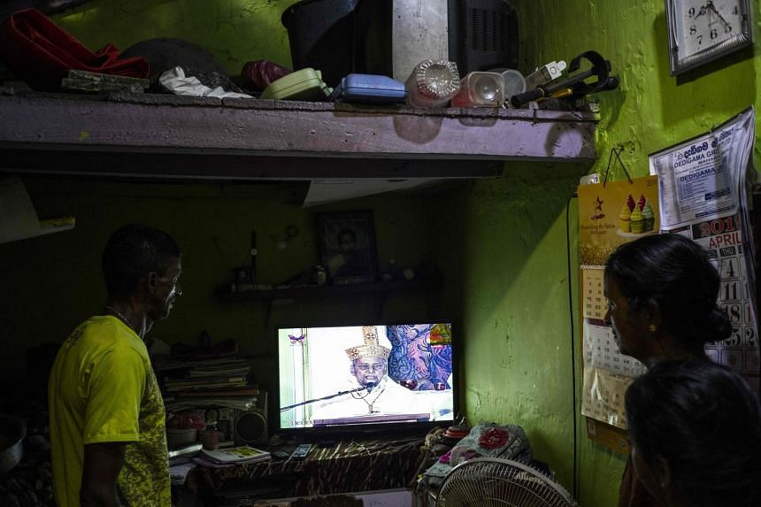 A Sri Lankan couple watching a live telecast of a private service conducted by the Archbishop of Colombo, Cardinal Malcolm Ranjith, in their house near St. Anthony's Shrine in Colombo on April 28, 2019.