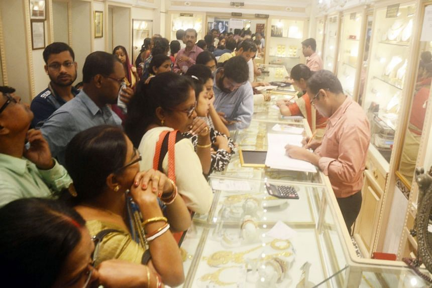 Customers buying gold in Kolkata in 2017. India's gold demand is expected to rise in the June quarter from a year ago due to a higher number of auspicious days for weddings and a fall in local prices ahead of a key festival, said the World Gold Counc