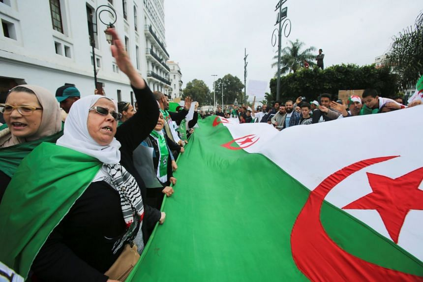 Demonstrators hold a flag and banners during an anti-government protest in Algiers, May 3.