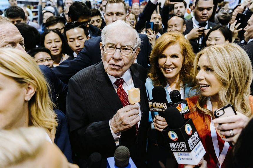 Warren Buffett (centre left) eats ice cream and mingles ahead of Berkshire Hathaway's annual meeting.