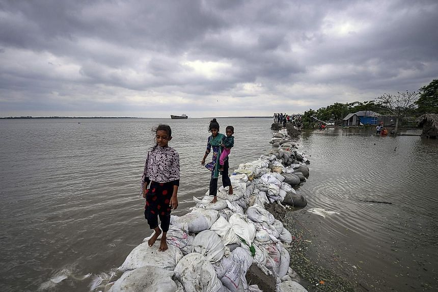 Children making their way across a sandbag embankment that was breached by high waters in Khulna, Bangladesh, yesterday. Cyclone Fani, one of the biggest to hit India in years, barrelled into Bangladesh yesterday after leaving a trail of destruction