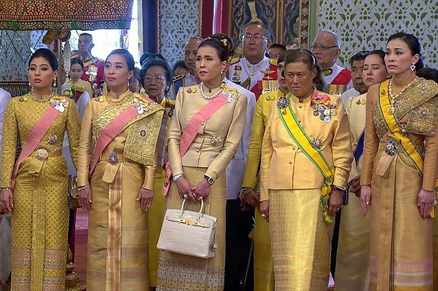 Thai people gathering to watch the coronation ceremony on a large screen outside the Grand Palace yesterday.
