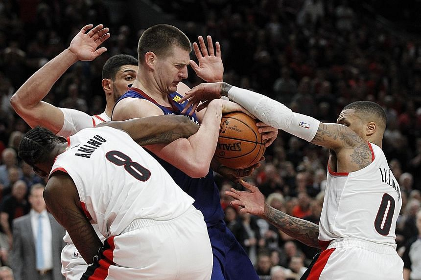 Portland players, including Al-Farouq Aminu and Damian Lillard, converging on Denver centre Nikola Jokic during Game 3 of their National Basketball Association Western Conference semi-finals at the Moda Centre in Portland on Friday. Portland won 140-137 t