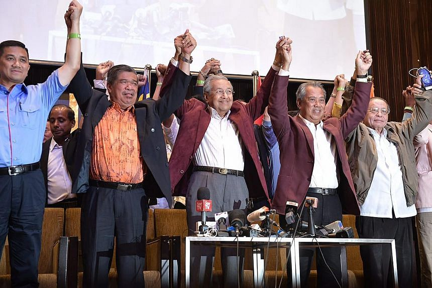 Tun Dr Mahathir Mohamad flanked by fellow Pakatan Harapan (PH) leaders (from left) Mohamad Sabu, Tan Sri Muhyiddin Yassin and Mr Lim Kit Siang on May 10 last year, after PH claimed victory in Malaysia's 14th general election. Though support has dropp
