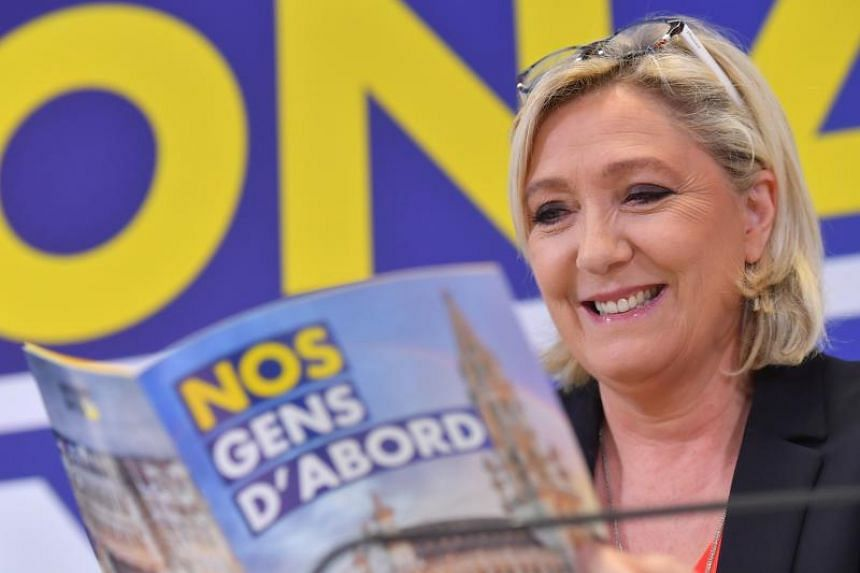 French far-right National Rally (Rassemblement National) party leader Marine Le Pen reads a political pamphlet from Belgium's Flemish right-wing Vlaams Belang party during a press conference in Brussels on May 5, 2019.