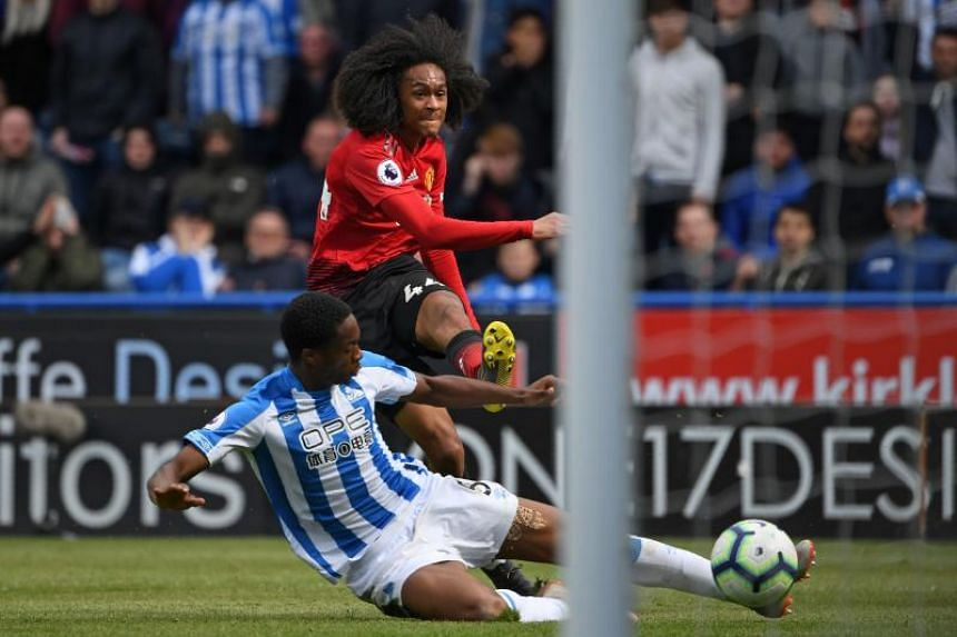 Manchester United's Dutch midfielder Tahith Chong shoots wide as Huddersfield Town's Swiss-born Dutch defender Terence Kongolo tries to block during the match between Huddersfield Town and Manchester United at the John Smith's stadium in Huddersfield