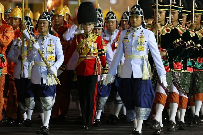 Thai Queen Suthida (centre) marches with royal guards during the procession.