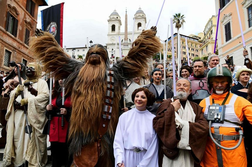 Actors impersonating Star Wars' Princess Leila (centre), Chewbacca (left) Obi-Wan Kenobi (second right) and other characters pose on the Rome's Spanish Steps during an event to mark Star Wars Day.
