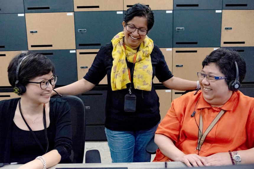 DBS customer service officers Lee Pei Ying (left) and Esther Tan (right) with DBS' Head of Customer Centre Geeta Sreeraman. DBS said more than 500 of its contact centre employees were reskilled to take on 13 new roles as part of the digital transfo