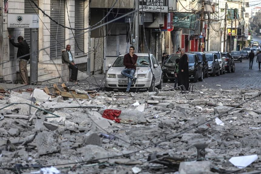 Residents gather in a debris-strewn street in Gaza City on May 5, 2019, that was hit during Israeli air strikes on the Palestinian enclave.