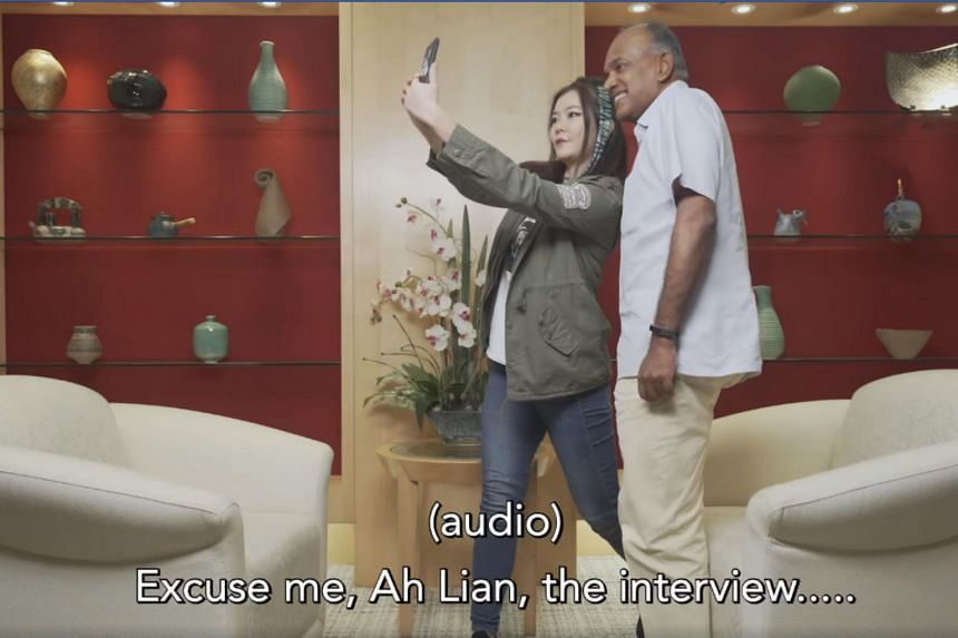 Ah Lian, actress Michelle Chong's alter ego, attempts to take a selfie with Law and Home Affairs Minister K. Shanmugam before an interview on the proposed fake news law. A person off-camera reminds her that she has an interview to conduct first.